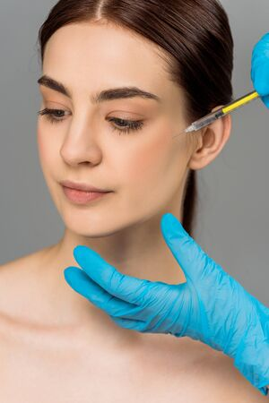 cropped view of plastic surgeon making beauty injection to attractive woman isolated on grey