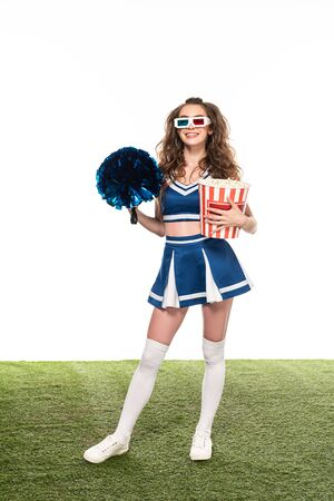 happy cheerleader girl in blue uniform and 3d glasses standing with popcorn and pompom on green field isolated on white
