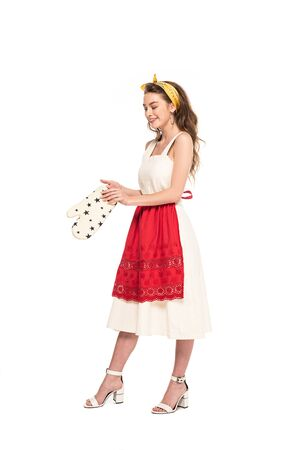 full length view of young happy housewife in dress and apron holding oven mitten isolated on white