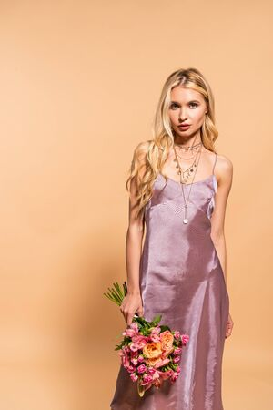 elegant woman in violet satin dress and necklace holding bouquet of flowers isolated on beige 免版税图像