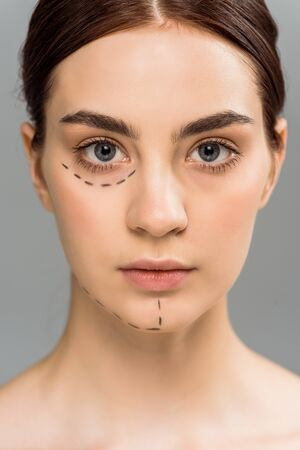 serious young woman with marks on face isolated on grey 스톡 콘텐츠