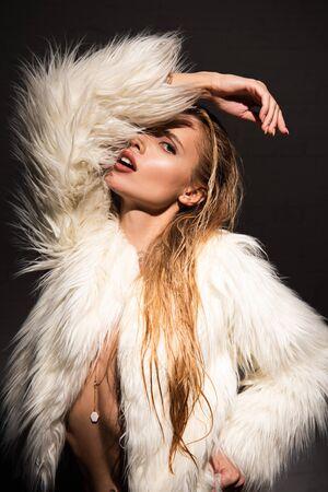 Mujer joven con cabello rubio en abrigo de piel sintética blanco aislado en negro