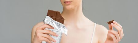 panoramic shot of young woman with problem skin holding chocolate bar and looking at camera isolated on grey