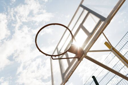 bottom view of basketball backboard under blue sky with clouds in sunny day