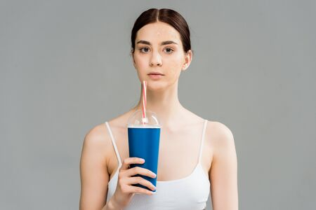 young brunette woman with problem skin holding plastic cup isolated on grey