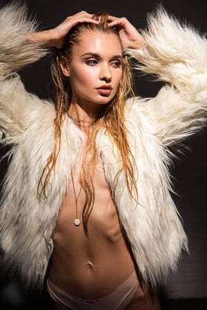sexy naked young woman with wet blonde hair in white faux fur coat posing isolated on black Stockfoto