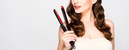 cropped view of beautiful brunette woman with curls holding straightening flat iron isolated on grey, panoramic shot