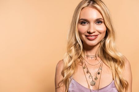 smiling blonde woman in violet satin dress and necklace isolated on beige