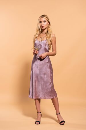 elegant blonde woman in violet satin dress and necklace holding cocktail on beige