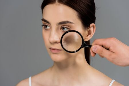 cropped view of man holding magnifier glass near woman with problem skin isolated on grey