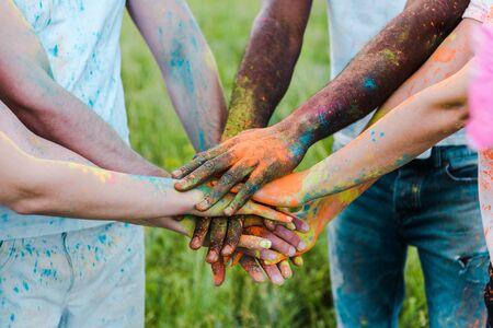 bijgesneden weergave van multiculturele vrienden met kleurrijke holi-verven die de handen in elkaar slaan