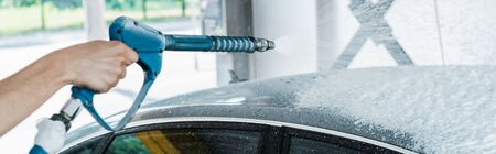 panoramic shot of car washer holding pressure washer with foam near car Foto de archivo - 128186025
