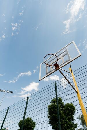 bottom view of basketball backboard under blue sky with clouds