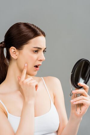 surprised young woman looking at mirror isolated on grey