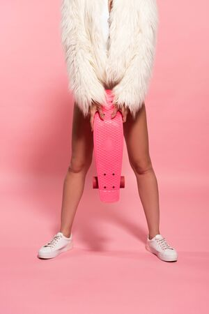 cropped view of girl in white faux fur coat holding penny board on pink