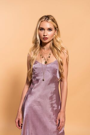 elegant blonde woman in violet satin dress and necklace posing isolated on beige 免版税图像