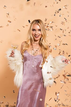 happy woman in white faux fur coat with cocktail standing under silver falling confetti on beige background