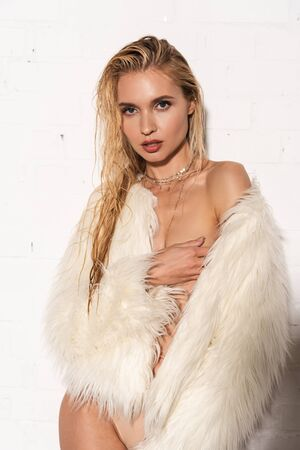 sexy naked young woman with wet hair in white faux fur coat touching breast on white background