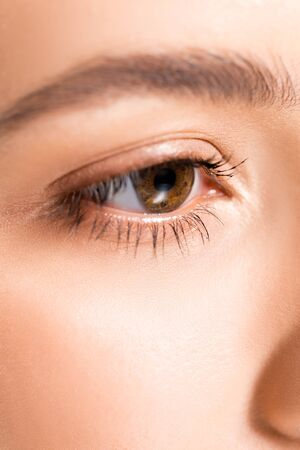 close up view of woman with brown clear eye and perfect skin