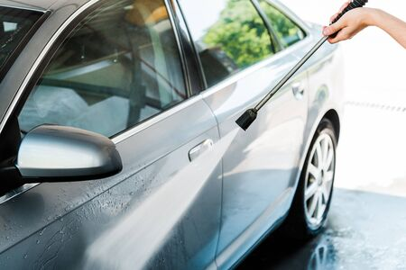 cropped view of car cleaner washing automobile with water pressure outside Foto de archivo - 128187139