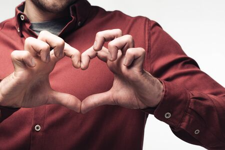 partial view of man showing heart sign with hands isolated on grey, human emotion and expression concept