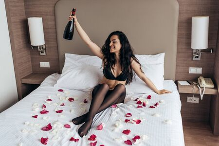 brunette girl in black lingerie sitting on bed covered with rose petals and holding bottle of champagne with smile in bedroom
