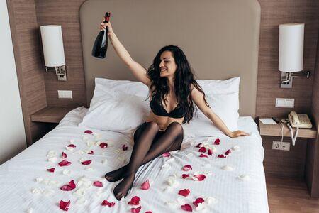 Chica morena en lencería negra sentada en la cama cubierta con pétalos de rosa y sosteniendo una botella de champán con una sonrisa en el dormitorio