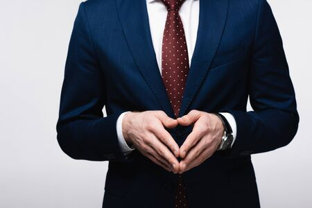 partial view of confident businessman showing steeple gesture isolated on grey, human emotion and expression concept Stockfoto