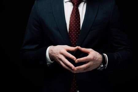 partial view of confident businessman showing steeple gesture isolated on black, human emotion and expression concept