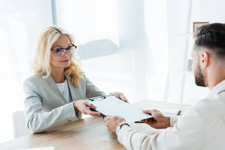 selective focus of attractive recruiter giving clipboard to man
