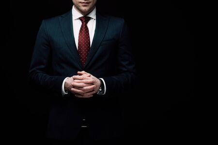 Vista parcial del empresario seguro de pie con las manos apretadas aisladas en negro, la emoción humana y el concepto de expresión Foto de archivo