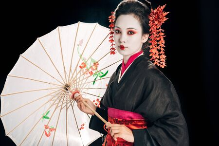 geisha in black kimono with red flowers in hair holding traditional asian umbrella isolated on black