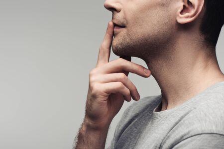 częściowy widok głupiego mężczyzny pokazującego znak ciszy wyizolowany na szarej, ludzkiej emocji i koncepcji ekspresji Zdjęcie Seryjne