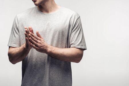 Vista recortada del hombre frotándose las manos aislado en gris, la emoción humana y el concepto de expresión Foto de archivo