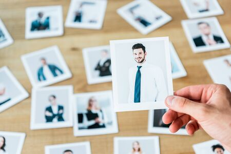 cropped view of recruiter holding photo with man in suit Stock Photo
