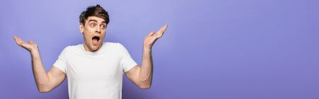 panoramic shot of handsome man showing shrug gesture on blue background