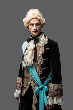 Apuesto caballero victoriano con peluca que se encuentran aisladas en gris