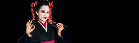 smiling beautiful geisha in black kimono with red flowers in hair holding chopsticks and showing okay sign isolated on black, panoramic shot