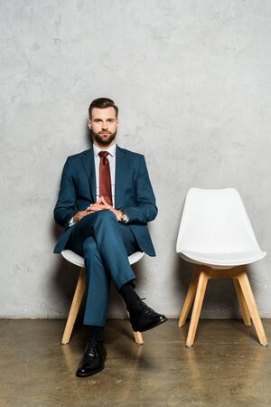 handsome bearded man sitting with crossed legs on chair in office