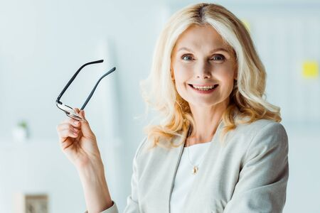 cheerful blonde woman holding glasses and looking at camera Stock Photo