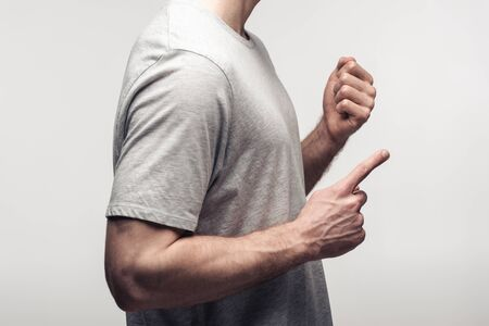 partial view of man holding fist and pointing with finger isolated on grey, human emotion and expression concept