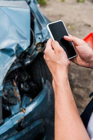 cropped view of man holding smartphone with blank screen near crashed car