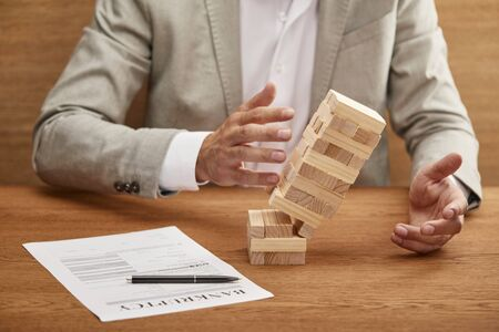 partial view of businessman in suit breaking tower made of wooden blocks near bankruptcy form