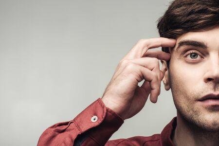 Captura recortada del hombre pensativo mirando a otro lado y tocando la cabeza aislada en gris, la emoción humana y el concepto de expresión