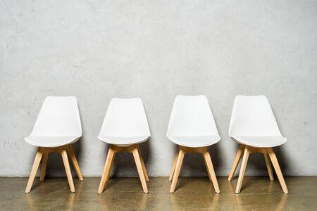 chaises blanches près du mur de béton gris avec espace de copie au bureau