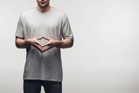 partial view of man in grey t-shirt showing steeple gesture while using body language isolated on grey, human emotion and expression concept