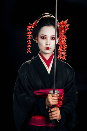 beautiful geisha in black kimono with red flowers in hair holding traditional katana isolated on black Stock Photo