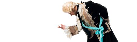 panoramic shot of handsome victorian gentleman in wig gesturing while bowing down isolated on white 免版税图像