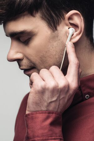 pensive man listening music in earphones with closed eyes isolated on grey Stock Photo