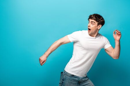 scared young man running away and looking back on blue background